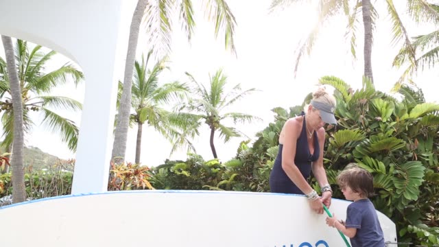 boy and his mother cleaning paddle board - sonnenschild stock-videos und b-roll-filmmaterial