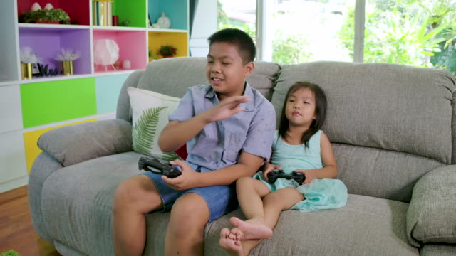 boy and his sister playing video game fight at home. - leisure games stock videos & royalty-free footage