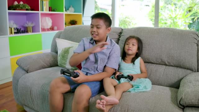 vídeos de stock e filmes b-roll de boy and his sister playing video game fight at home. - jogo de lazer