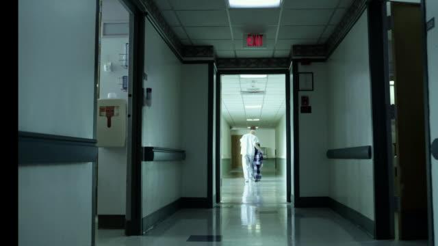 Boy and male nurse walking in hospital corridor
