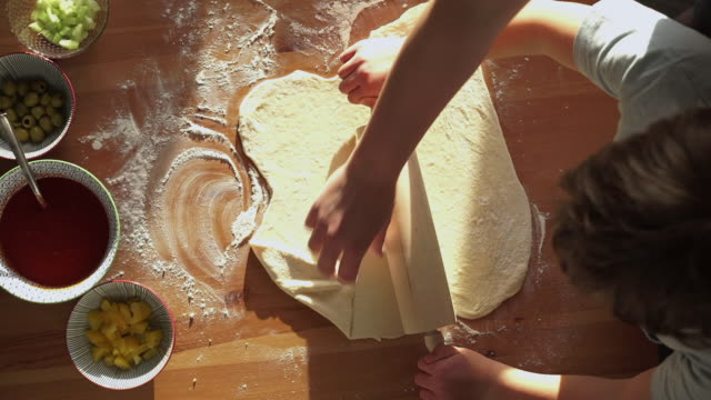 stockvideo's en b-roll-footage met boy and mother are kneading a pizza dough with a rolling pin - table top view