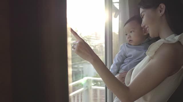 vídeos y material grabado en eventos de stock de niño y madre mirando a través de la ventana - son