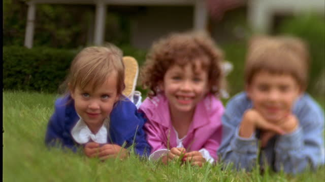 a boy and two girls smile while relaxing in green grass. - hand am kinn stock-videos und b-roll-filmmaterial