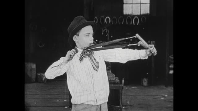 1922 boy annoys car mechanic (buster keaton) - catapult stock videos & royalty-free footage