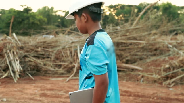 boy asian walking go to construction site with holding tablet , concept my dream engineering, slow motion - adult imitation stock videos and b-roll footage
