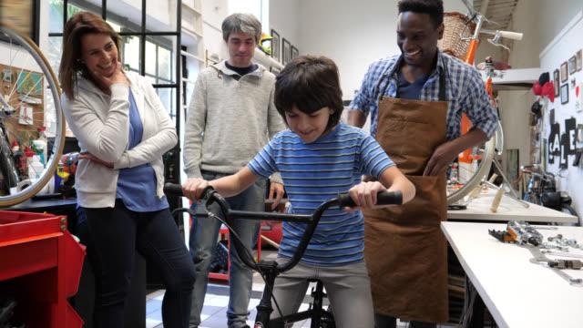 vidéos et rushes de garçon dans un magasin de vélo avec ses parents et le sympathique vendeur en lui donnant pour essayer sa première bicyclette vous cherchez excité - acheter