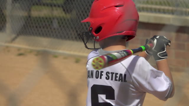 vídeos de stock e filmes b-roll de boy at bat and batting in a little league baseball game. - slow motion - camisola de basebol