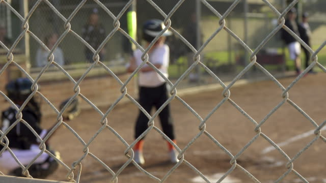 Boy at bat and batting in a little league baseball game.
