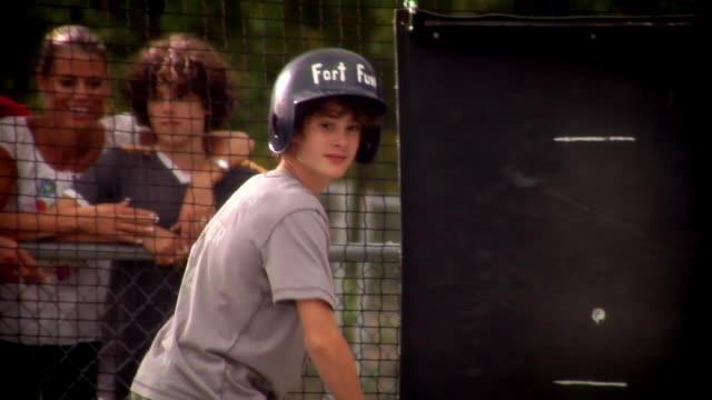 boy at bat in batting cage as family members watch outside cage / hitting pop-flies / hitting line-drive - sportaktivitet bildbanksvideor och videomaterial från bakom kulisserna