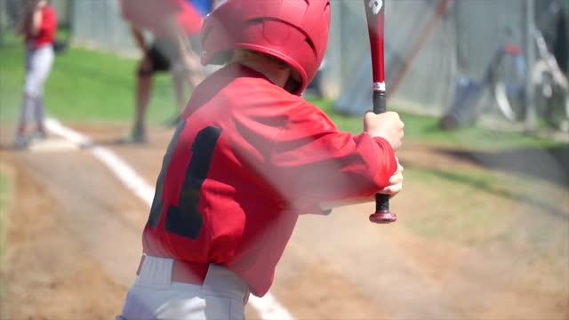 a boy at bat while playing little league baseball. - slow motion - hitting点の映像素材/bロール