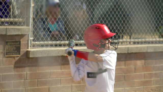 a boy at batter in a little league baseball game. - hitting stock videos & royalty-free footage