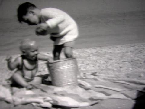 vídeos de stock e filmes b-roll de 1934 boy at beach pours cup of water on brother - 1930