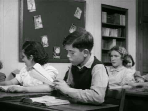 vídeos de stock, filmes e b-roll de b/w 1951 boy at desk standing up + preparing to throw paper airplane in classroom / educational - mischief