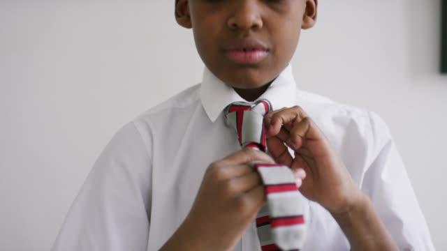 vidéos et rushes de un garçon à la maison se prépare pour l'école - shirt and tie