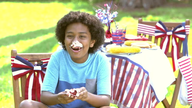 Boy at July Fourth picnic enjoying cupcake