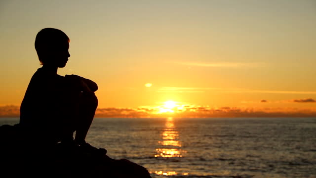 boy at sunset by the sea - one boy only stock videos & royalty-free footage