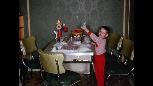 stockvideo's en b-roll-footage met 1955 montage boy (4-5) at table, checking out chocolates / toronto, canada - 1955
