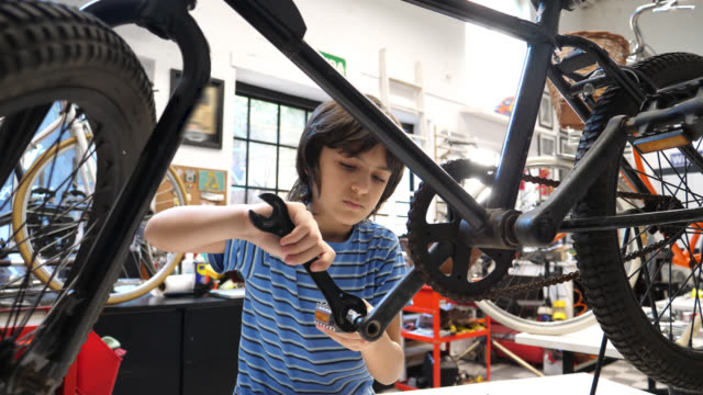 boy at the family business bicycle repair shop changing the pedals on his bike using a tool and looking very focused - repairing stock videos & royalty-free footage