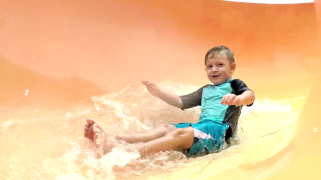 boy at water park sliding down giant water slide - water slide stock videos & royalty-free footage