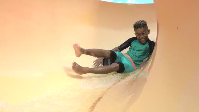 Boy at water park sliding down waterslide