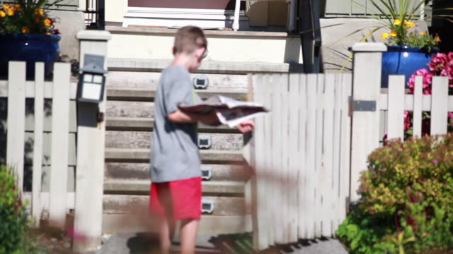 vídeos y material grabado en eventos de stock de boy barefoot delivering newspaper to a front door on a sunny spring day. - kelly mason videos