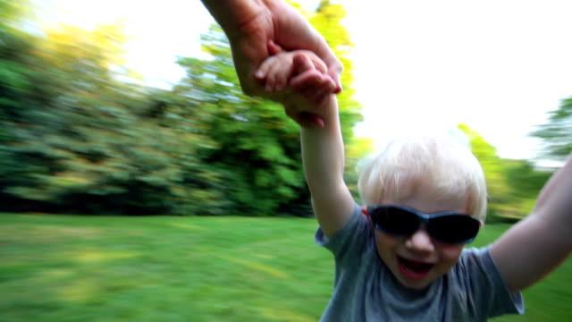 boy being spun around. hd - 高處 個影片檔及 b 捲影像