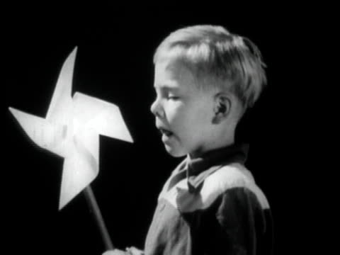 b/w cu boy blowing on pinwheel / usa - girandola video stock e b–roll