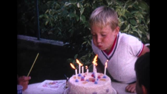 vidéos et rushes de 1964 boy blowing out birthday candles - gâteau d'anniversaire