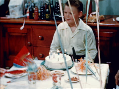 1946 boy blowing out candles on birthday cake at party / starts cutting cake / industrial - birthday candle stock videos & royalty-free footage