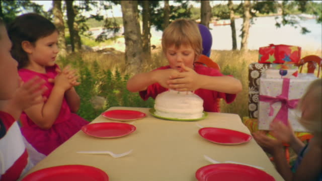 MS Boy blowing out candles on birthday cake while his friends applaud / Vinalhaven, Maine, USA