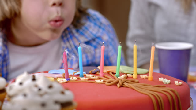 Boy blowing out the candles on a birthday cake