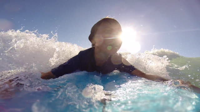A boy body boarding in the waves. - Slow Motion