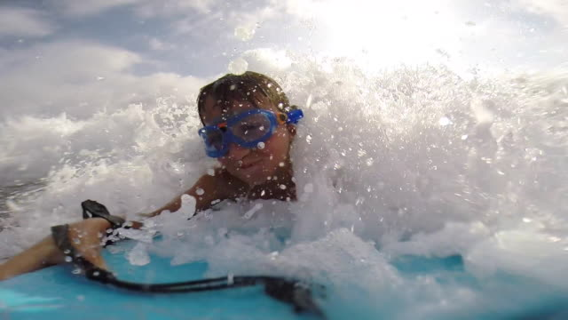 a boy body boarding in the waves while where goggles at the beach. - blonde hair stock videos and b-roll footage