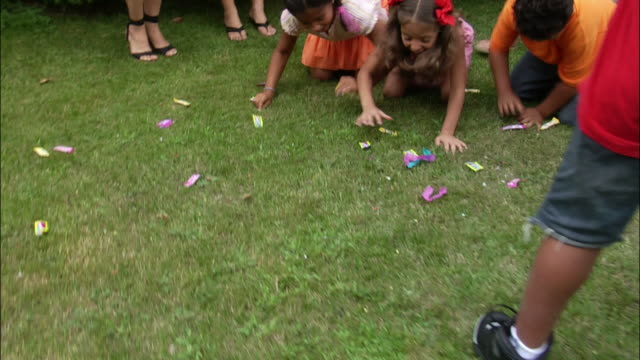 Boy breaking pinata open with stick and candy falling to ground / children crawling on grass and grabbing candy / New Jersey