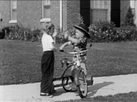 B/W 1950 boy breaking up fight between little girl + little boy with cowboy hat on sidewalk / educ.