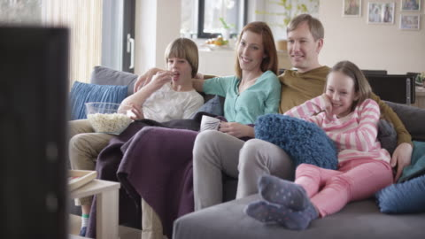 boy bringing popcorn to family sitting on the sofa - television stock videos & royalty-free footage