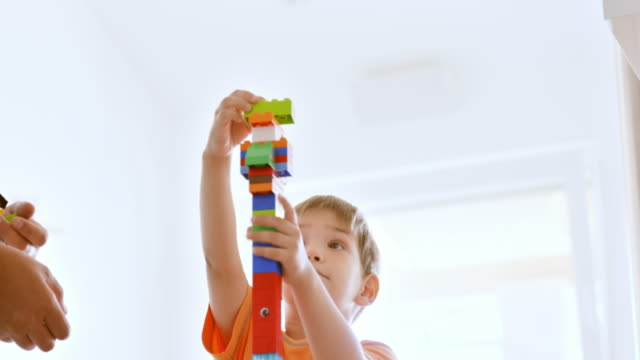 Boy building a high plastic brick tower with father