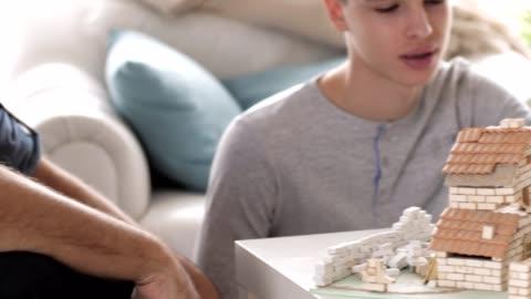vídeos y material grabado en eventos de stock de niño construyendo una casa en miniatura en casa - ladrillo