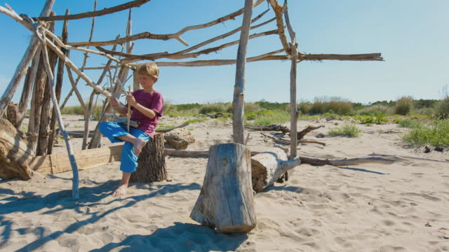 WS Boy building beach hut from driftwood