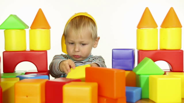 boy builds a house out of blocks
