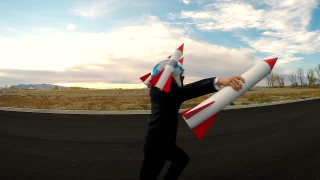 boy businessman holding rockets stellt sich das fliegen vor - abheben aktivität stock-videos und b-roll-filmmaterial