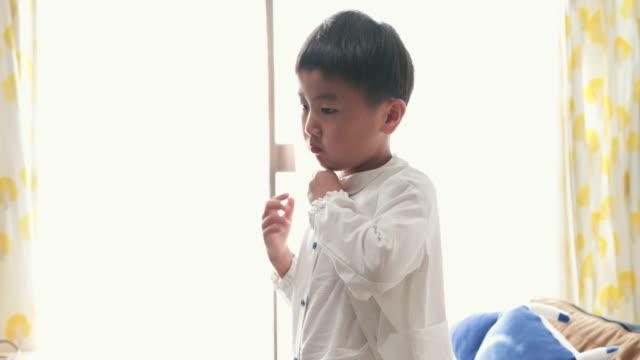 朝、自宅でシャツをボタンで押す少年 - 日本の学生服点の映像素材/bロール