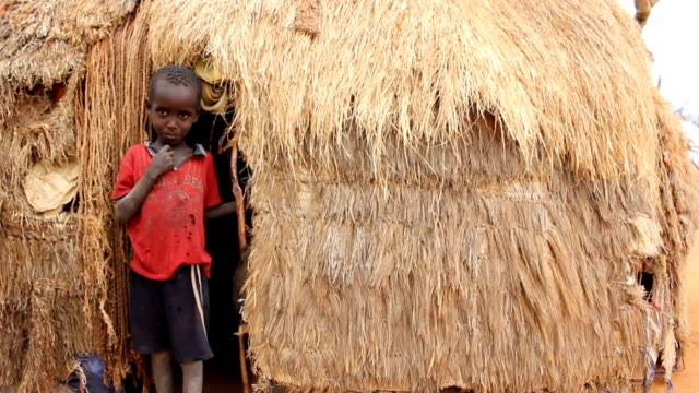 boy by the entrance of his straw hut on august 02 2011 in road from garisa to dadaab kenya - kenia stock-videos und b-roll-filmmaterial