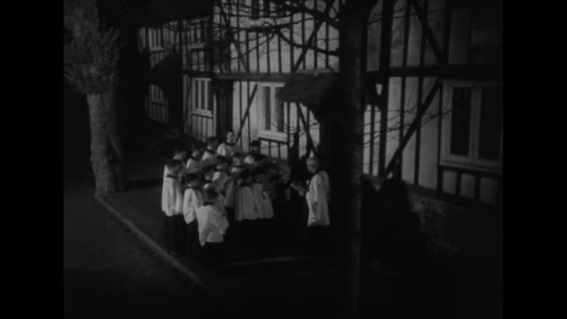 boy carolers in robes exit church and they walk to half-timbered house where the homeowners open windows and lean to listen / vs the boys' faces as... - carol singer stock videos & royalty-free footage