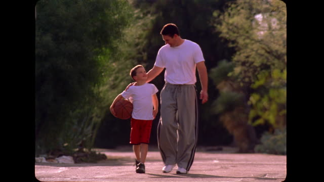 A boy carries a basketball as he walks down a road with his father.