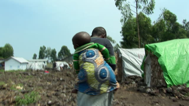 stockvideo's en b-roll-footage met ms boy carrying baby on back across camp, refugee camp, goma, congo - carrying