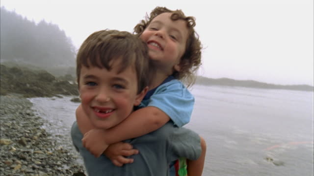 vidéos et rushes de cu boy (6-7) carrying brother (2-3) on back on beach / north haven, maine - maine