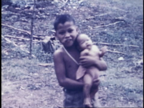 boy carrying infant out of tent, smiling at camera / guam - guam video stock e b–roll