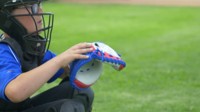 Boy catcher dropping ball with American flag glove in a little league baseball game, red, white, blue, stars. - Slow Motion