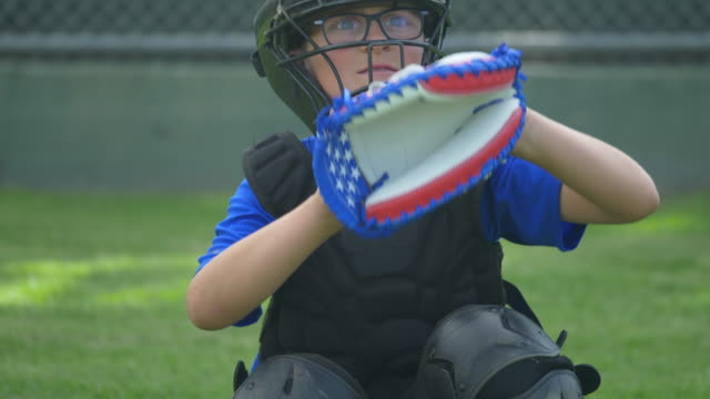 boy catcher dropping ball with american flag glove in a little league baseball game, red, white, blue, stars. - slow motion - catching stock videos & royalty-free footage